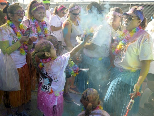 Runners in Saturday's Color Vibe 5K run throw colored corn starch on each other.