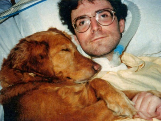 "Service dog Addie comforts Mike Luber in 1994 after Mike, who has muscular dystrophy, underwent a tracheotomy. Addie is the star of children's book ""Where's Addie?"""