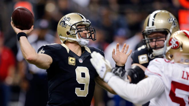 New Orleans Saints' quarterback Drew Brees (9) passes under pressure from San Francisco 49ers' linebacker Aaron Lynch in the 49ers' 27-24 win in overtime Sunday. Brees passed for 292 yards and three touchdowns.