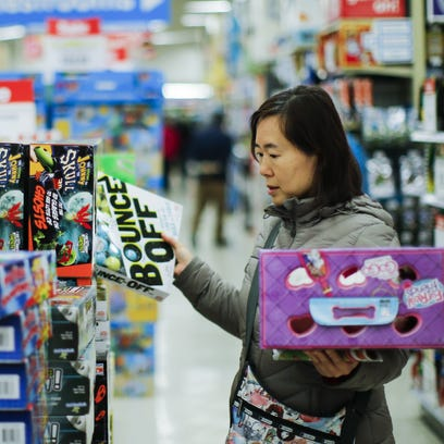 """A shopper looks for gifts inside of the Toys""""R""""Us store"""