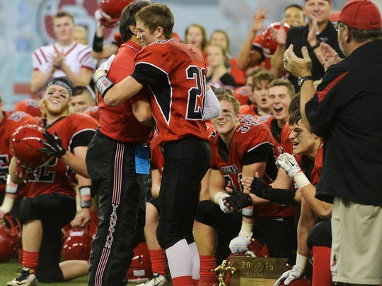 Yankton head coach, Arlin Likness hugs Tanner Frick after he was named MVP following their 21-20 overtime win over Pierre in Friday's class 11AA football championship at the DakotaDome in Vermillion, Nov 13, 2015.