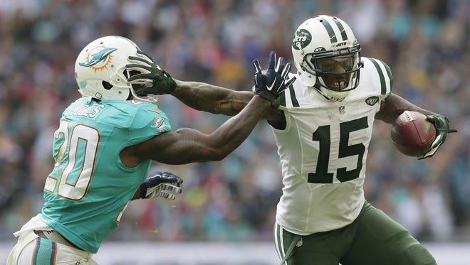 New York Jets' Brandon Marshall, right, fends off Miami Dolphins' Reshad Jones during the NFL football game between the New York Jets and the Miami Dolphins and at Wembley stadium in London.