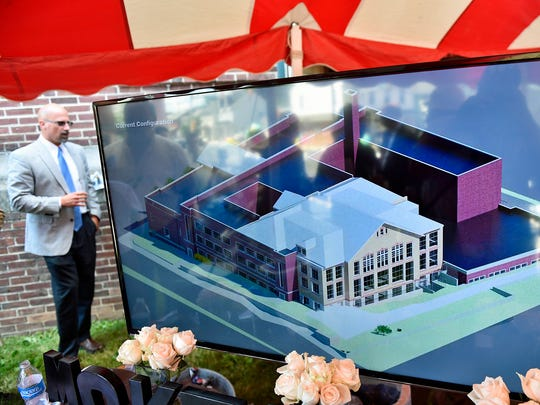 Lance Kegerreis, Chambersburg Area Development Corp., stands in the background as plans for the Rose Rent Project play on a TV screen during  a groundbreaking ceremony on Friday, June 9, 2017. The project will convert the former Central Junior High School into high-end lofts and apartments.