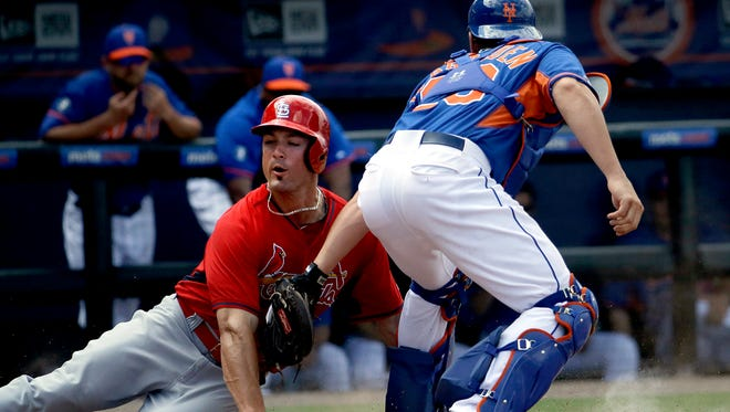 St. Louis Cardinals' Randal Grichuk, left, is tagged out at home plate by New York Mets catcher Taylor Teagarden on a hit by Pete Kozma in the fifth inning of an exhibition spring training baseball game, Wednesday, March 12, 2014, in Port St. Lucie, Fla. (AP Photo/David Goldman)