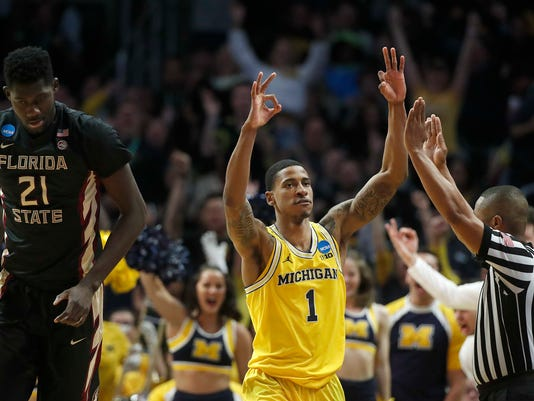 Michigan guard Charles Matthews, center, gestures after hitting a 3-pointer as Florida State center Christ Koumadje, left, stands near him during the second half of an NCAA men's college basketball tournament regional final Saturday, March 24, 2018, in Los Angeles. (AP Photo/Jae Hong)