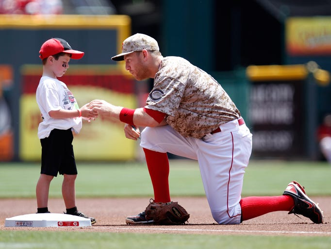 Cincinnati Reds third baseman Todd Frazier (21) hands the ball to a child prior to the game against the Toronto Blue Jays at Great American Ball Park.