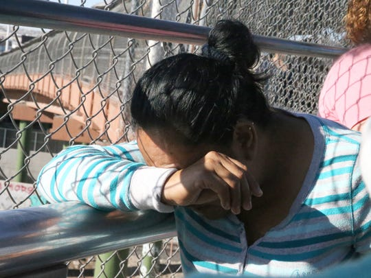 An asylum seeker from Mexico buries her head in her arm as she waits for word from U.S. Customs and Border Protection officials at the summit of the Paso Del Norte Bridge and port of entry June 20. She, a second woman and their children eventually were escorted into the facility.