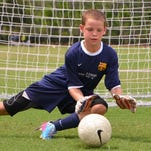 Adam Henry of Fort Myers makes a save during the FC Barcelona camp held at Fenway South in Fort Myers last summer. Henry is one of five locals selected to play in a tournament in Spain this month.