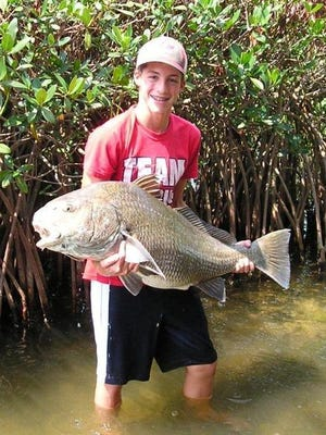 "Matthew Holmes, 15, landed this 50-pound black drum while fishing alone recently in a 10-foot jon boat in Sykes Creek on Merritt Island. It took Holmes 40 minutes to get the fish to the boat. ""The hard part was getting it into the boat. I grabbed it by the tail a couple of times, but it was just too big to handle. I finally got it by the gill plate and pulled it in,"" he said.  For FLORIDA TODAY"