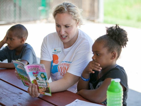 Jennifer Harmeyer, an Everybody Wins! Iowa program manager, reads to Candi Clem, 6, a second-grader at Howe Elementary in Des Moines during the MLK Park Summer Program in 2014.