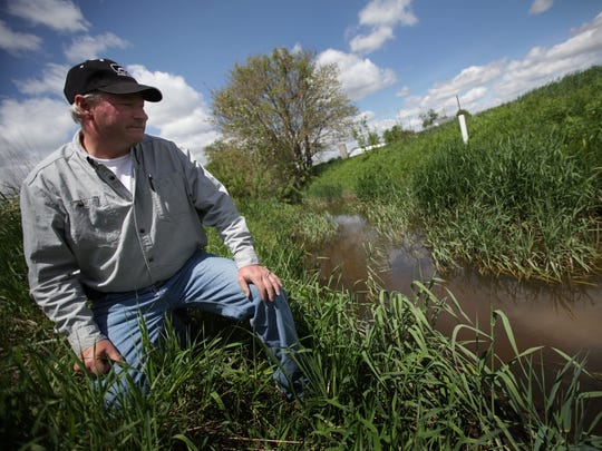 """Doug Darling, 54, stands by the Amos Palmer drain on his farm in Monroe County where he grows wheat, corn and soybeans. Proposed revisions to the federal Clean Water Act by the EPA and Army Corps of Engineers have Michigan farmers like Darling concerned about additional paperwork, cost and time.New water rules proposed by the EPA have Michigan farmers concerned. They could designate even minor wetlands or drainage ditches on farms as """"Waters of the United States,"""" requiring a federal permit, delay and cost to modify."""