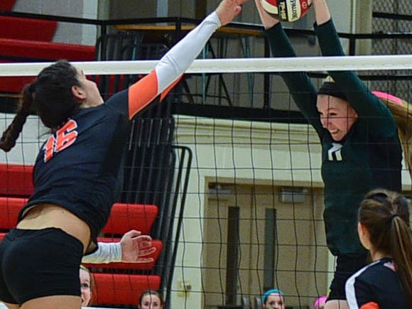 West High's Emily Halverson, right, blocks a spike by West Des Moines Valley's Courtney Twit in a regional final Tuesday in Newton.
