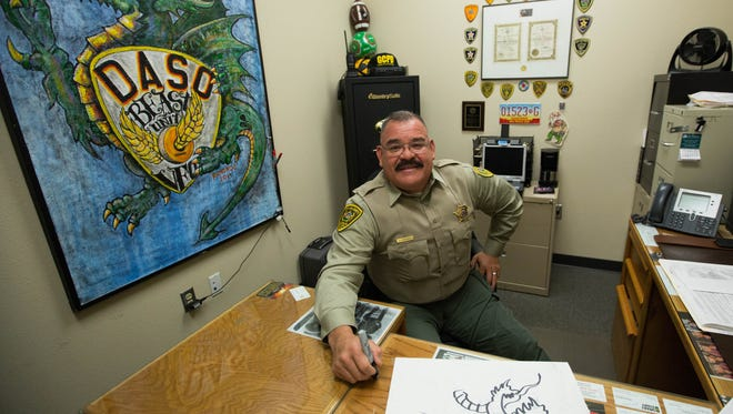 Daniel Ramondo, a Doña Ana County Sheriff's deputy, who draws caricatures of fellow deputies as well as past and present sheriffs, in his office at the DASO offices where the walls are covered in his artwork. Thursday Jan 11, 2018.