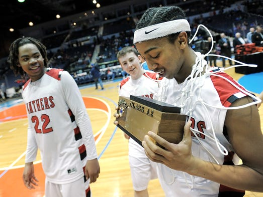 Geneva's Akia Jackson, right, admires the championship trophy following the Class A2 sectional final played at the Blue Cross Arena on Sunday.