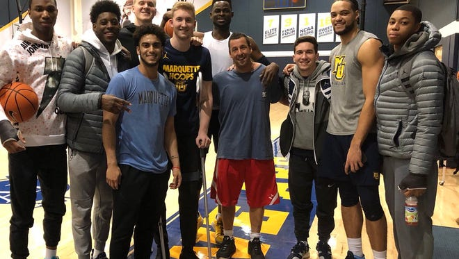 Comedian Adam Sandler poses with members of the Marquette men's basketball team at the Al McGuire Center.