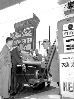 Gas began to pour from the 12 pumps at the official opening of the Cotton States Servicenter at 1399 Thomas on 9 Apr 1954, and the first tankful went to Mayor Frank T. Toby (Right).  F.H. Hamilton, Jr. (Left), president of the Cotton States Tire & Oil Co., watched as Vance M. Thompson Jr. (Second Left), general sales manager, filled the tank at the huge car-home appliance unit.  The two men in background are unidentified.  The Commercial Appeal files.