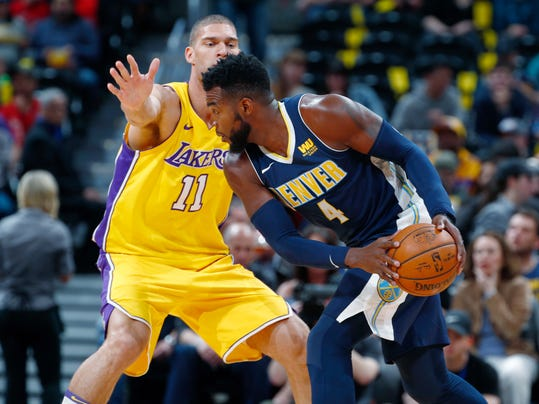 Denver Nuggets forward Paul Millsap, front, is defended by Los Angeles Lakers center Brook Lopez during the first half of an NBA basketball game Friday, March 9, 2018, in Denver. (AP Photo/David Zalubowski)