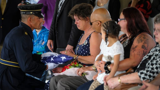 A member of the 3rd Infantry Old Guard presents the folded flag to Spc. Zachary Clouser's mother Deb Etheridge during his funeral at Arlington National Cemetery, Friday, April 22, 2016. John A. Pavoncello photo