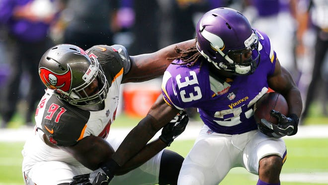 Minnesota Vikings running back Dalvin Cook (33) tries to break a tackle by Tampa Bay Buccaneers defensive end Robert Ayers (91) during the first half of an NFL football game, Sunday, Sept. 24, 2017, in Minneapolis.