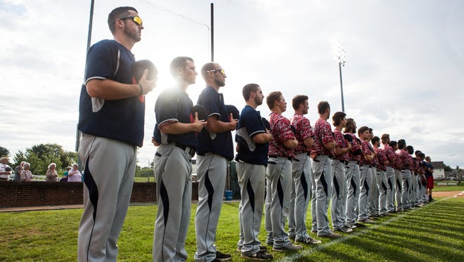 Waynesboro Generals head coach, D.J. King, left, and  assistant coach Matt Williams, second from left, stand together during the National Anthem before the beginning of their team's game against Strasburg on Wednesday, July 8, 2015.