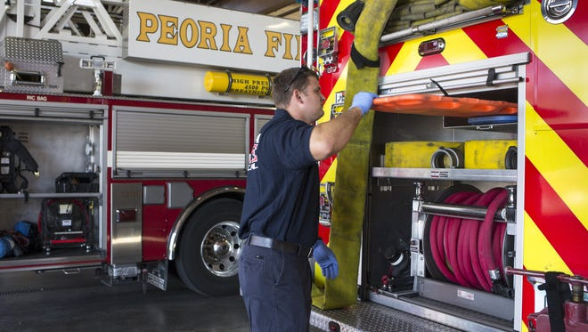 Peoria firefighter Darin Fox checks medical supplies July 7, 2015, on Engine 191 at Peoria Fire Department Station 191, 8065 W. Peoria Ave., Peoria.