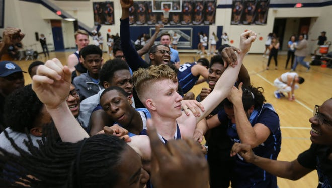 Chapin's Andre Carrillo is mobbed by teammates after hitting the game-winning basket as time expired Tuesday.
