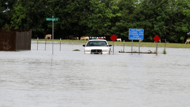 A police car is seen partially submerged in flood water in the Oak Creek Subdivision after heavy overnight rain showers Wednesday, May 28, 2014, in Carencro.