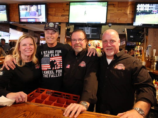 Jennifer Knapp, owner, Veteran Andy Barcelona, Rob Johsnon, owner and Chris Maltese, owner, pose behind the bar. The TVs are tuned to soccer, game shows and golf. Woody's Tavern in Farmingdale didn't show football on Sunday in respect for veterans on Veterans Day weekend. In place of the games, the bar will hold a special concert featuring members of the New Jersey-based country group After the Reign, with a portion of the proceeds going to the Green Beret Foundation through Special Forces Association Chapter 19. Farmingdale, New Jersey. Sunday, November 12, 2017. David Gard