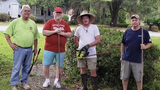 From left are Walt Gibbs, Darrell Russell, Ben Steel and Clay Bishop, working to help Russell, a disabled military veteran, with his yard work.