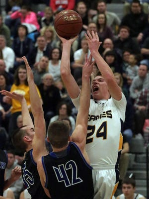Sheboygan County Christian's Brayden VanEss (24) launches a shot by Hilbert's Jack Halbach (42) Thursday in Brown Deer.