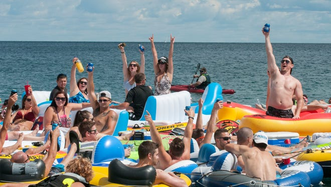 People celebrate as they start the floatdown Sunday, Aug. 21 at Lighthouse Beach in Port Huron.