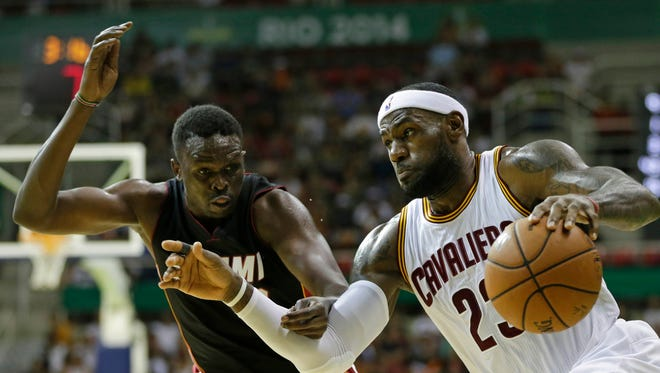 Cleveland Cavaliers' LeBron James (right) drives past Miami Heat's Luol Deng in a preseason game Saturday. James had seven points and three rebounds in the Cavaliers' 122-119 win.