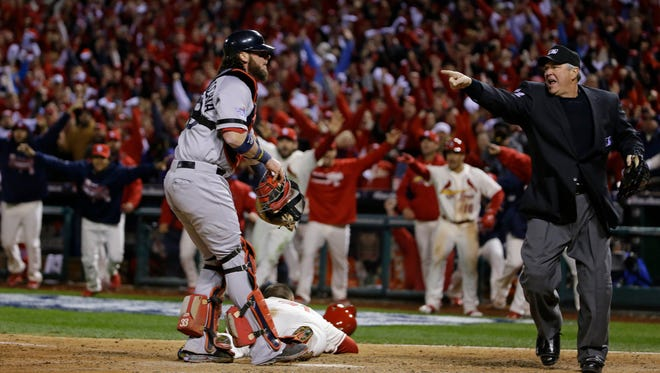 Home plate umpire Dana DeMuth, right, makes an obstruction call allowing St. Louis Cardinals' Allen Craig, on ground, to score the game-winning run in Game 3 of the World Series on Saturday in St. Louis.