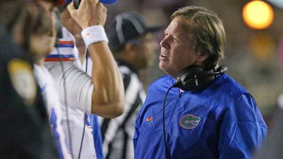 Florida coach Jim McElwain talks with Luke Del Rio on the sideline after his team didn't convert on third down against Florida State in the third quarter of an NCAA college football game, Saturday, Nov. 26, 2016, in Tallahassee, Fla. Florida State won 31-13. (AP Photo/Steve Cannon)