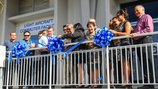 Gov. Eddie Calvo, visiting officials from the Commonwealth of Northern Mariana Islands, and others take part in a ribbon cutting ceremony to officially open the Light Aircraft Commuter Facility on Thursday, Oct. 1. The old building, near the Guam International Airport Authority terminal, underwent $250,000 in renovations to handle aircraft operations for lighter planes weighing 12,500 pounds or less.