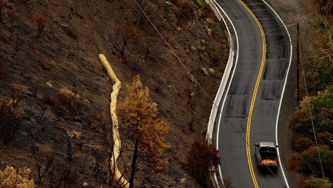 A pickup carrying sandbags makes its way up Silverado Canyon Road near a burned-out section of mountain in a rural part of Orange County, Calif., on Tuesday. A powerful Pacific storm swept through the region, bringing the threat of mudslides in areas left bare by wildfires.