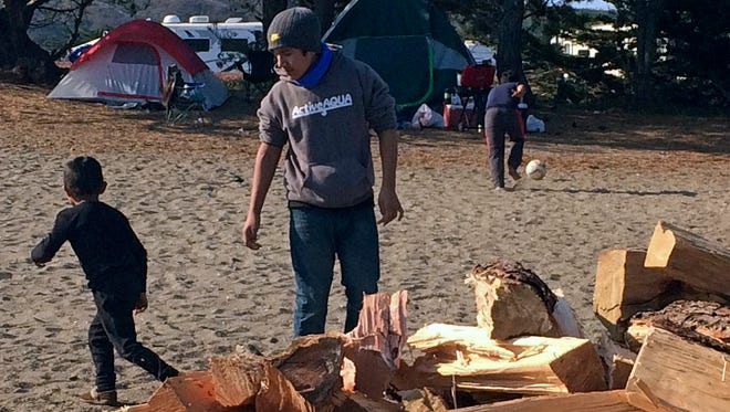 Children of families who evacuated from fire zones far to the south play on a beach at Bodega Bay on Thursday. Tents and firewood were donated by local people for the hundreds of fire evacuees showing up.
