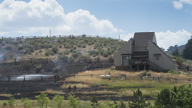 Firefighters tend to hot spots after containing a fire near County Road 29 west of Loveland on July 7. Local fire crews responded to more than 130 calls during a summer-long burn ban.