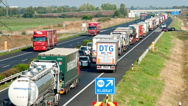 A long line of vehicles wait on the M1 motorway near the border between Hungary and Austria near Mosonmagyarovar, northwest of Budapest, Hungary, on Aug. 31, 2015. The line has reached 18.5 miles as every vehicle capable of smuggling people is checked at the border after 71 migrants were found dead in a truck Thursday.