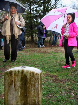 Edith Ann Clark Moore, left, and her great-niece Janiah Waters stand at the grave of former slave William Holland, who helped build the Stones River National Cemetery. Moore spoke about her family ties to the former slaves who established Cemetery Community in connection with building the national cemetery.