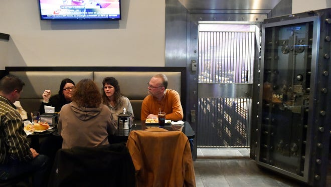 From left, Brad and Glenda Lentz of Dover, Karen Smith of Jackson Township, and Warrington Township residents Jodi Stambaugh and Gary Rodgers eat dinner next to the vault door at The Vault Pizza & Grill in West Manchester Township. The restaurant was formerly an M&T Bank branch.