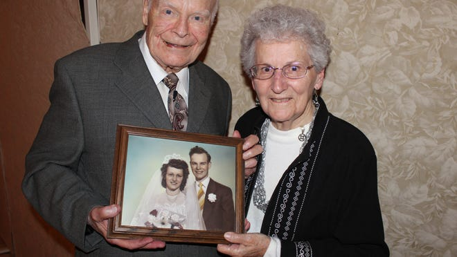 Robert and Bernice Fehrenbach of Marshfield pose with their wedding photo during a dinner Oct. 19 at Our Lady of Peace Catholic Church in Marshfield that honored couples married more than 50 years.
