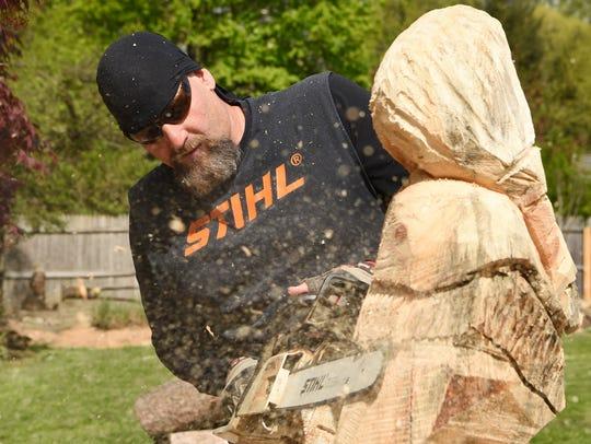 Don Mesuda, a chainsaw carver, blocks out a Native