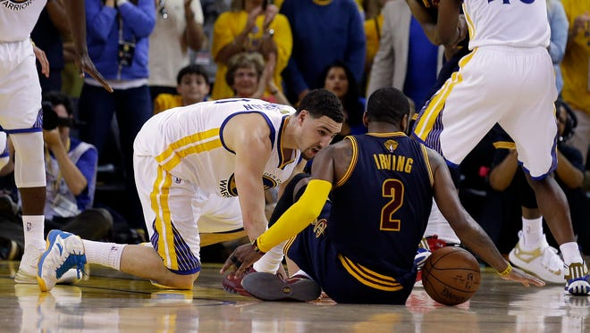 Cleveland Cavaliers guard Kyrie Irving (2) tries to control the ball next to Golden State Warriors guard Klay Thompson during overtime of Game 1 of basketball's NBA Finals in Oakland, Calif., Thursday, June 4, 2015. Irving left the game with an injury right after this play.