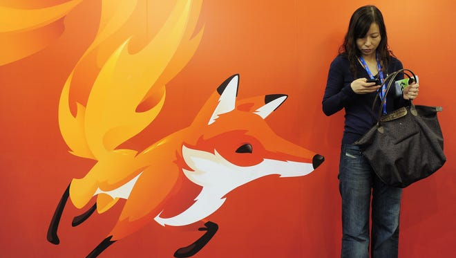 A woman stands in front of a poster of Mozilla Firefox.