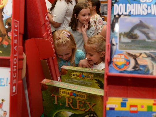 Libby Nelson, age 6, left, and Emma Tempel, age 6, look at books during the Lincoln Elementary School Ice Cream Social and Book Fair in May.