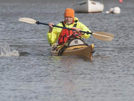 Denis Carmody paddles in his kayak during a sunny winter