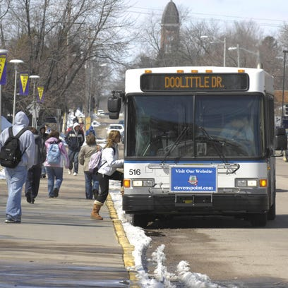 A student boards the city bus at a stop on the University