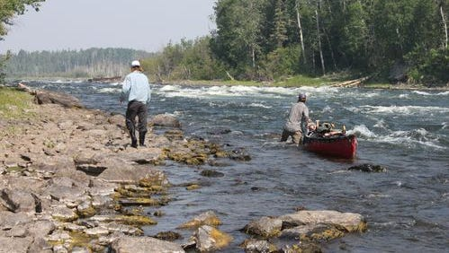 Luke Kimmes, left, and Winchell Delano walk up a stretch of rapids on the Churchill River.