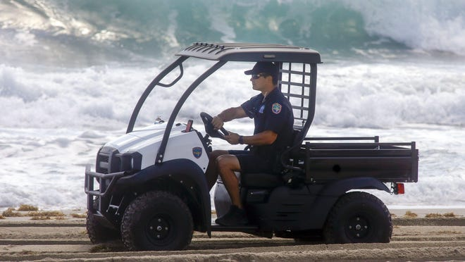 A police officer patrols Midtown Beach in March to make sure no one enters after the Town of Palm Beach decided to close its beaches due to the coronavirus.